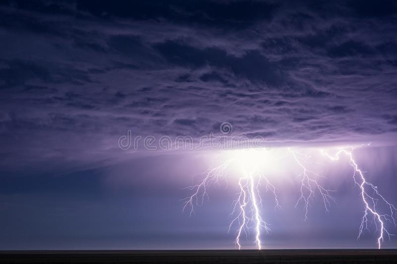 Powerful lightning bolts strike from a summer thunderstorm. Powerful lightning bolts strike from a summer thunderstorm at night near Eads, Colorado royalty free stock photos