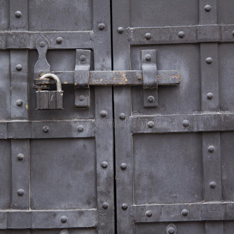 Metal antique durable door with a lock. Powerful metal door with rivets and padlock royalty free stock photography