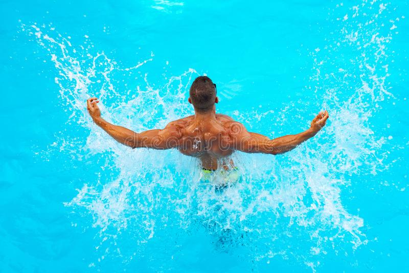 Powerful muscular male figure on blue beach background. Beautiful young man relaxing on beach. Young man Swimming Pool royalty free stock image