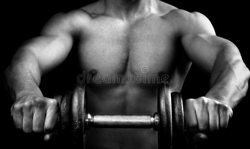 Powerful muscular man holding a dumbbell stock image