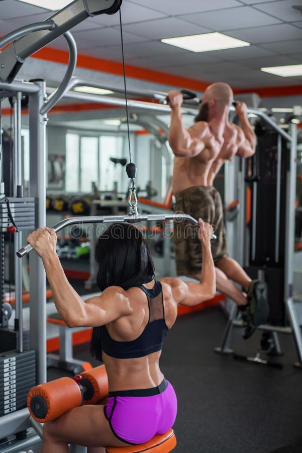 Powerful, muscular, strong, guy and girl, train back. The guy performs pull-UPS, the girl makes a craving for the head.  royalty free stock images