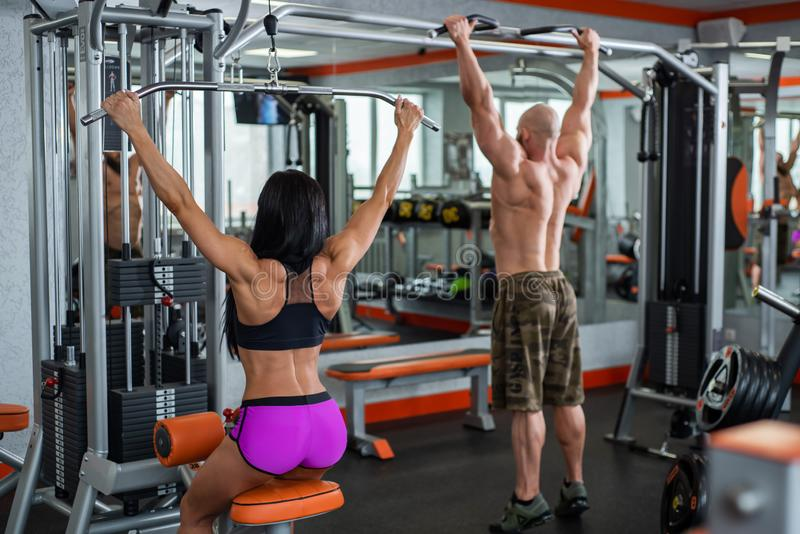 Powerful, muscular, strong, guy and girl, train back. The guy performs pull-UPS, the girl makes a craving for the head.  royalty free stock photos