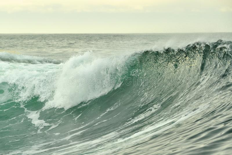 Powerful ocean wave breaking. Wave on the surface of the ocean. Wave breaks on a shallow bank. Natural background stock photography