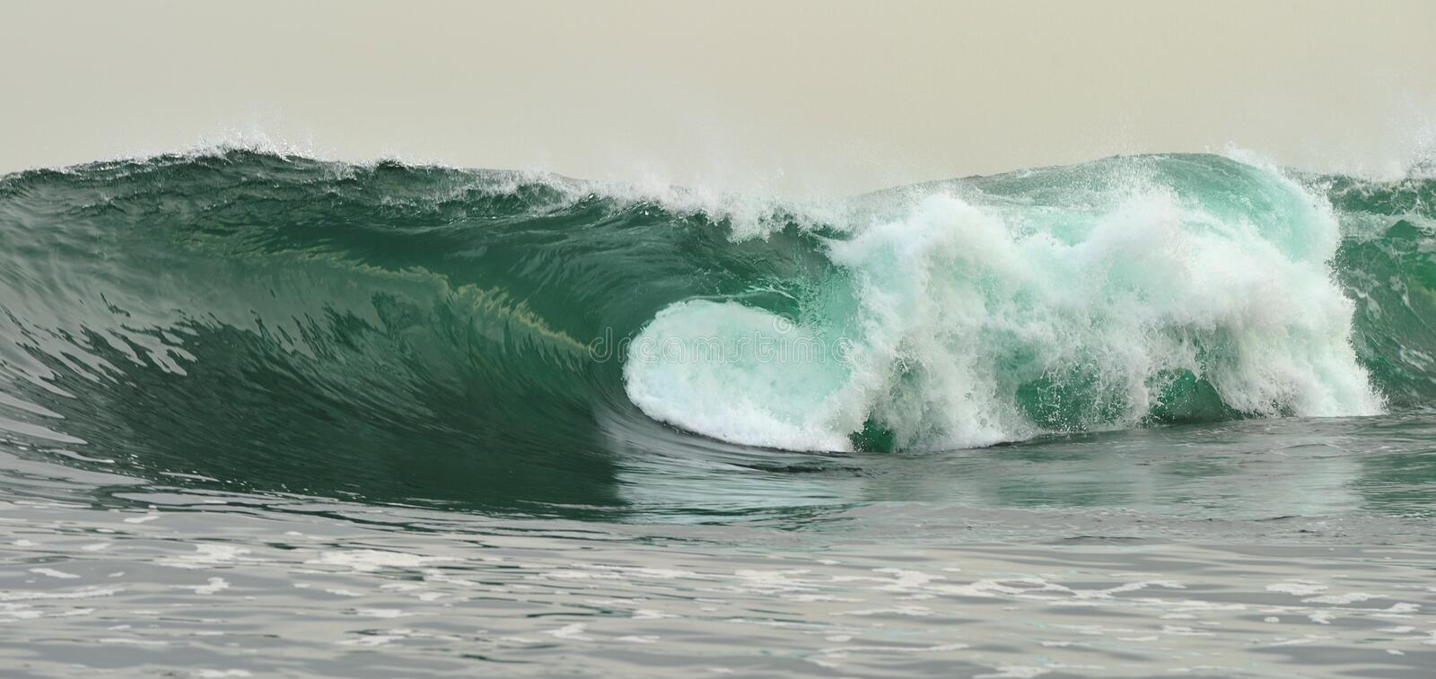 Powerful ocean wave breaking. Wave on the surface of the ocean. Wave breaks on a shallow bank. Natural background stock image