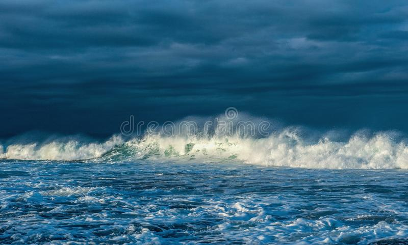 Powerful ocean wave on the surface of the ocean. Wave breaks on a shallow bank. Stormy weather. Clouds sky background. Seascape stock photography