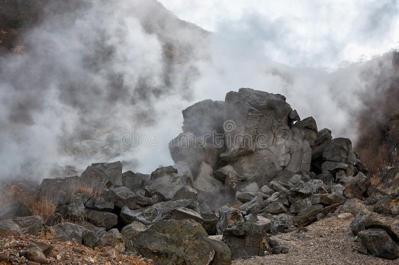 The sulfurous fumes of Owakudani  Valley.  Hakone area. Honshu. Japan. Powerful outbursts of fumes and sulfur among the rocks in the  Owakudani  Valley.  Hakone royalty free stock photos