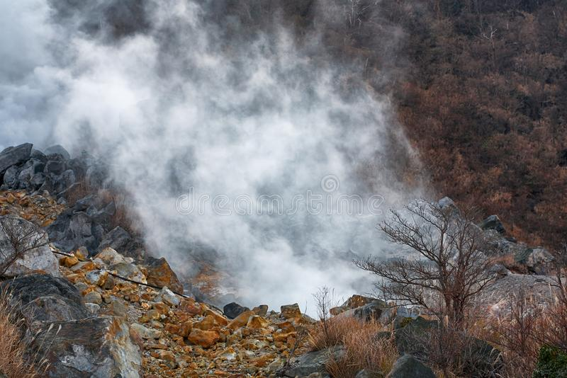 The sulfurous fumes of Owakudani  Valley.  Hakone area. Honshu. Japan. Powerful outbursts of fumes and sulfur among the rocks in the  Owakudani  Valley.  Hakone royalty free stock image