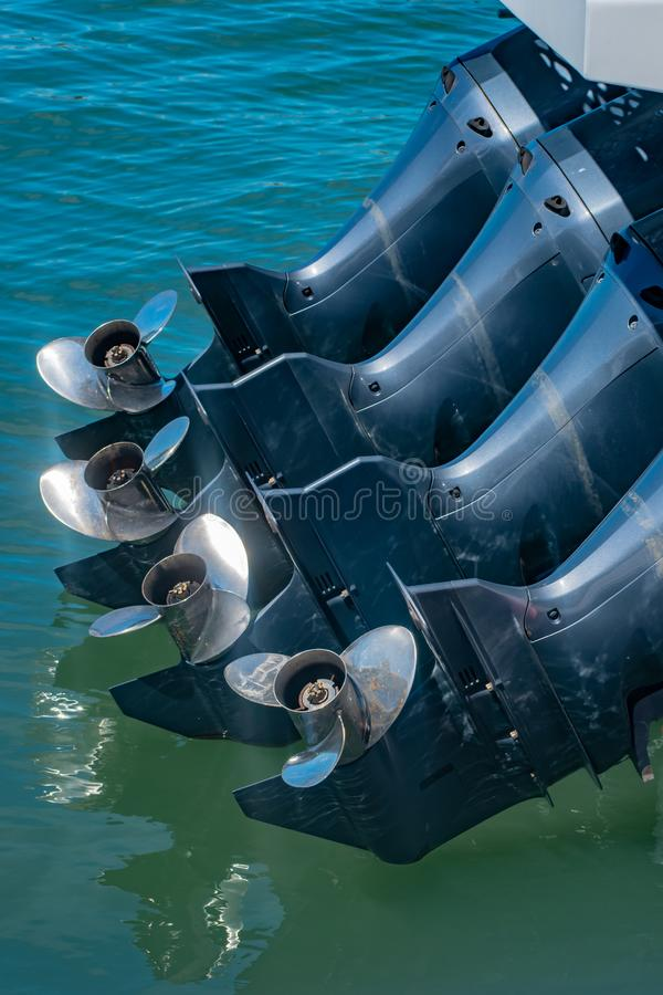4 powerful propellor engines on the hull of a boat. The hull of a boat with 4 powerful propellor engines out of the water for mooring stock photo
