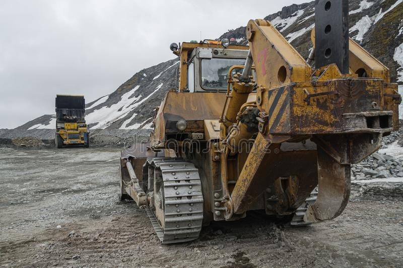 Powerful quarry bulldozer and gigat dump truck operating in the apatite mine in the Murmansk region stock photo