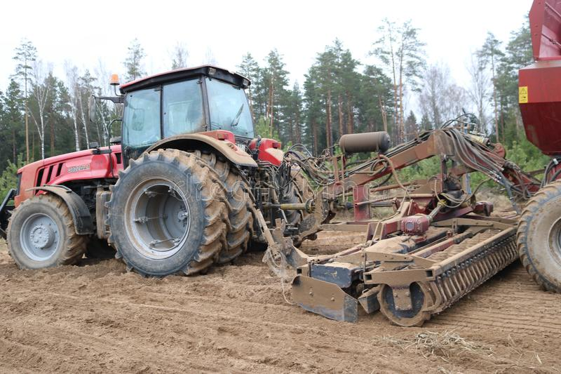 A powerful red tractor with a connected seeding unit, a combine, a drill with large wheels plows the land, sows crops, performs ag stock photo