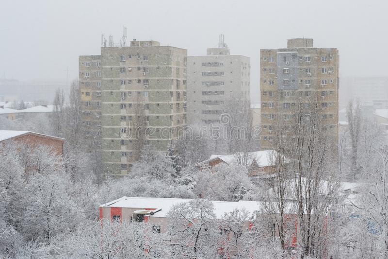 Powerful snow storm in Bucharest, Romania, with tall apartment buildings barely visible from the rapidly falling snow flakes. Old urban buildings during a royalty free stock photography