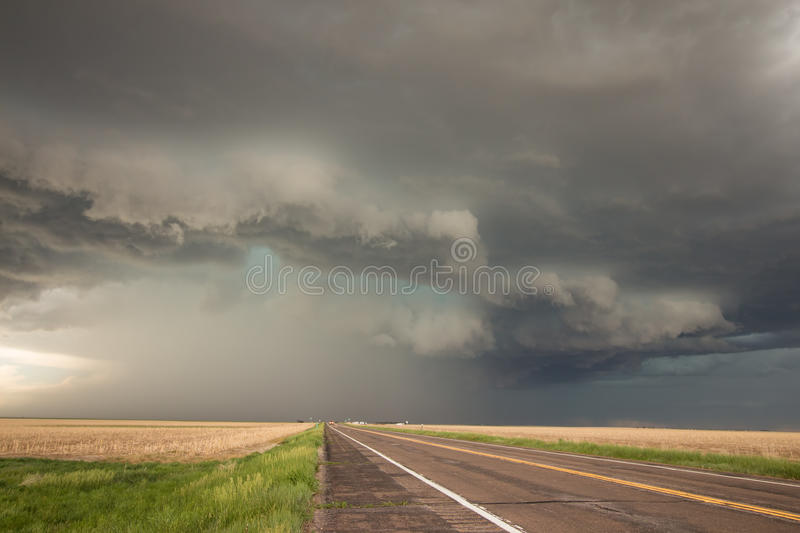 A powerful supercell thunderstorm looms over the highway. A powerful supercell thunderstorm looms over a highway in eastern Colorado royalty free stock photography
