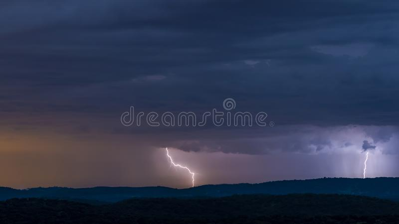 Powerful thunderstorm over hills at night. Breathtaking view of powerful thunderstorm over hills in dark evening stock image