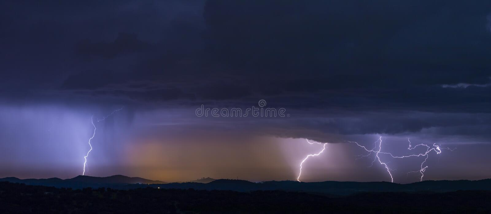 Powerful thunderstorm over hills at night. Breathtaking view of powerful thunderstorm over hills in dark evening stock photo