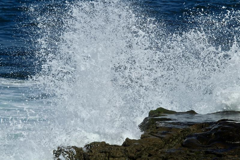 Powerful wave crashing on a rock in the ocean royalty free stock photos