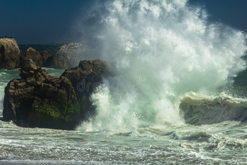 Powerful wave crashing on the rocks at a beach in Malibu stock photo
