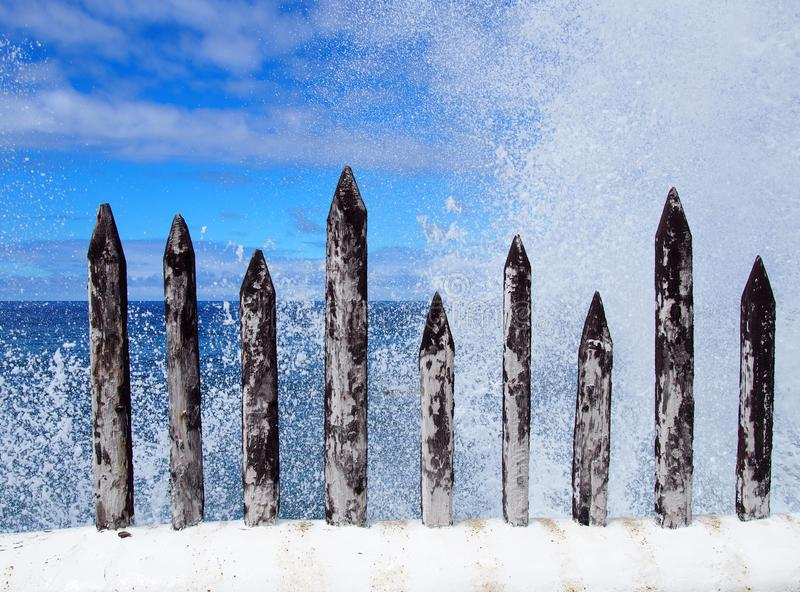 powerful waves breaking over sharp wooden spikes royalty free stock photo
