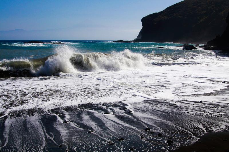 Powerful white foaming waves hit black lava sand beach in the evening sun. Vallehermosa, La Gomera, Canary Islands royalty free stock image