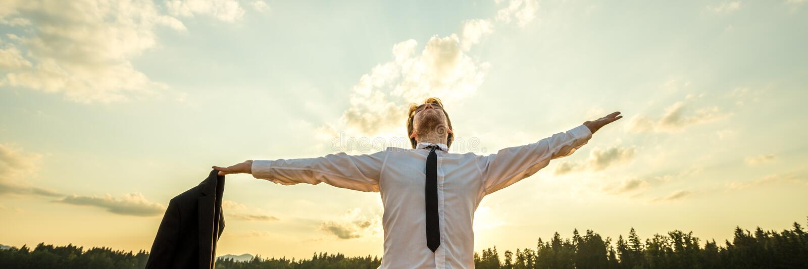 Powerful young businessman standing under evening sky stock photos