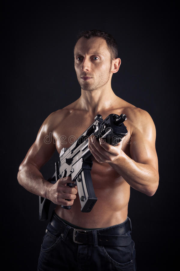 Powerful young man with rifle stock images
