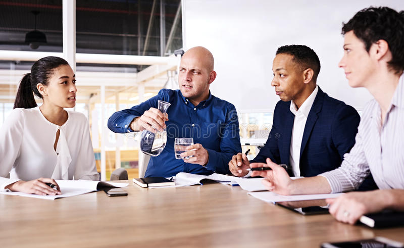 Powerful young woman talking with the attention of three colleagues royalty free stock photography