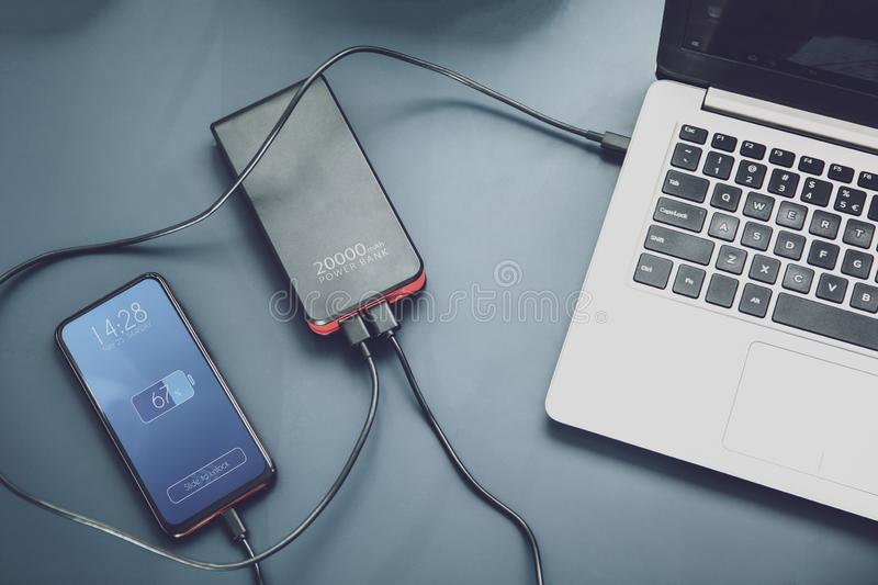 Powerfull power bank charges two devices at one time. Via USB-C connection. Interface on the screen was created in graphic program stock photography