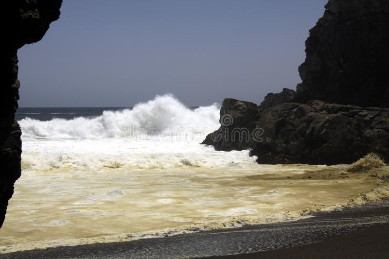 Powerfull waves crashing on a rock and splashing water in the air on remote black lava sand beach at Pacific coastline royalty free stock photography