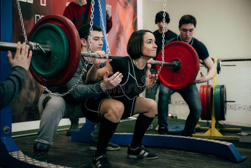 powerlifter的少妇运动员蹲杠铃 库存图片
