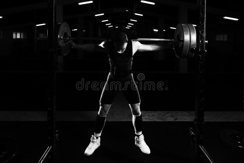Powerlifter, das Übung für Beine mit Barbell tut lizenzfreies stockfoto