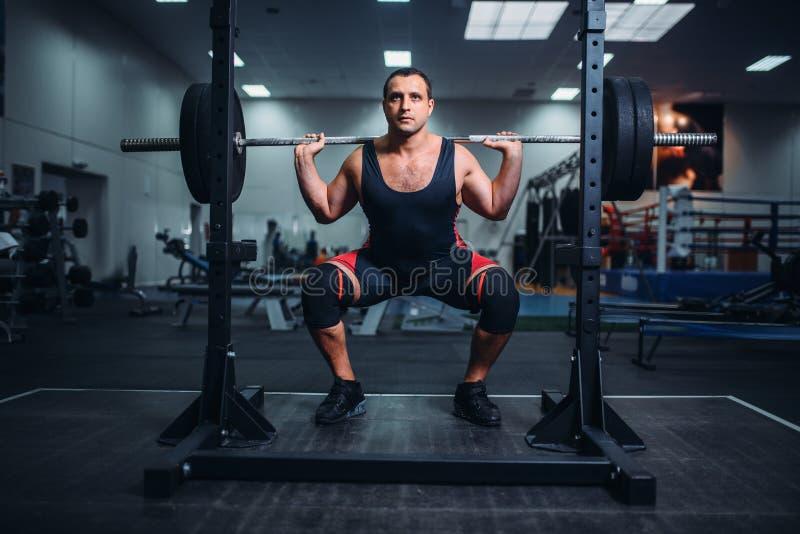Powerlifter, das Hocken mit Barbell in der Turnhalle tut lizenzfreies stockbild