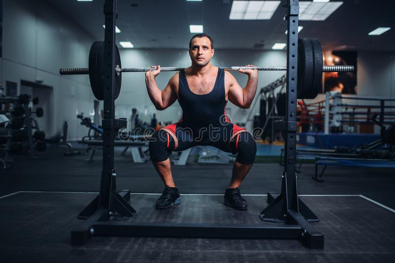 Powerlifter doing squats with barbell in gym royalty free stock image