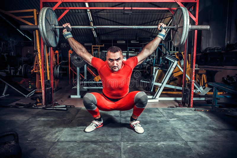 Powerlifter met sterke wapens die gewichten opheffen stock foto's