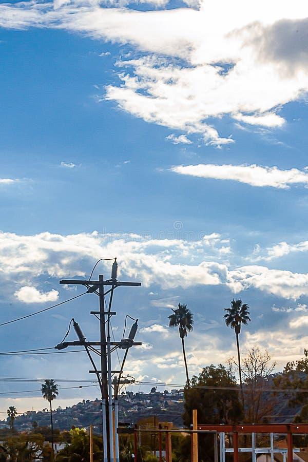 Powerline e palo con le palme e la costruzione, contro il pendio di collina fotografia stock