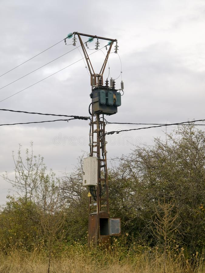 Powerlinepol med isolatorer i ett skogområde arkivbild