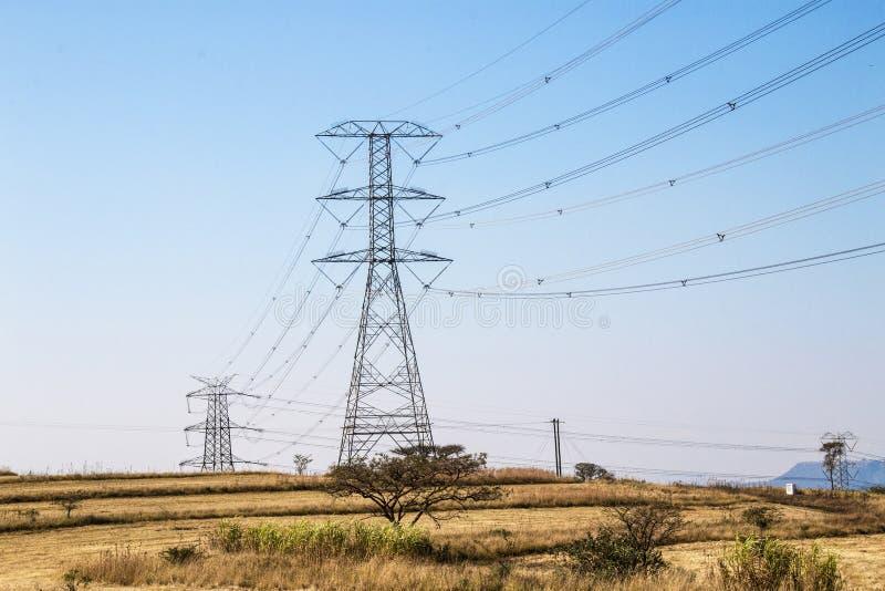 Powerlines e piloni elettrici sul paesaggio di inverno fotografia stock libera da diritti