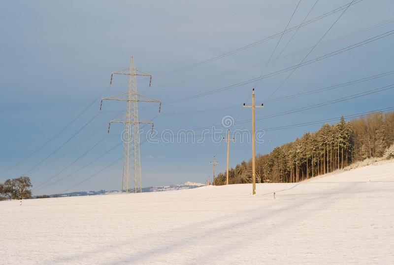 Powerlines elettrici che attraversano in un paesaggio di inverno fotografia stock libera da diritti