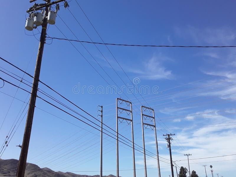 Powerlines Intersect a Blue Sky along a Lonely Highway stock photography