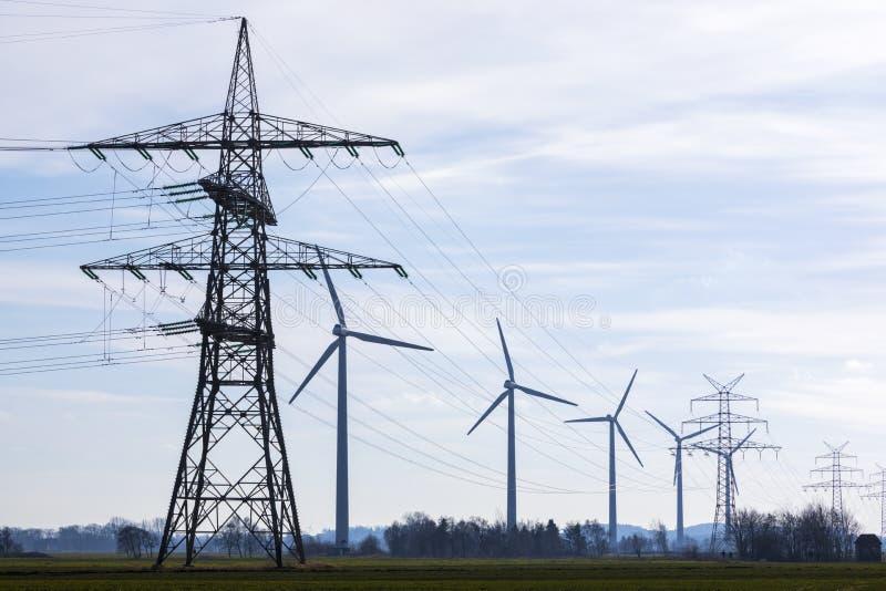Powerlines och vindturbiner arkivfoto