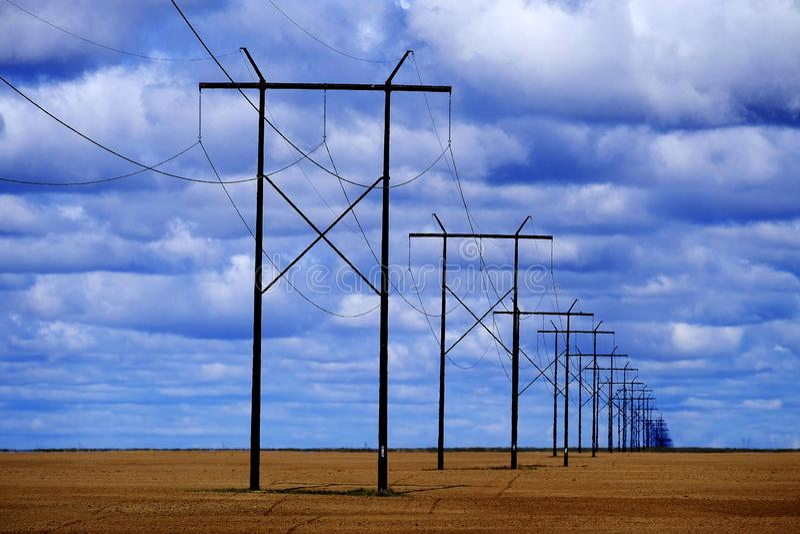 Powerlines op Gebied met Blauwe Hemel en Wolken royalty-vrije stock foto's