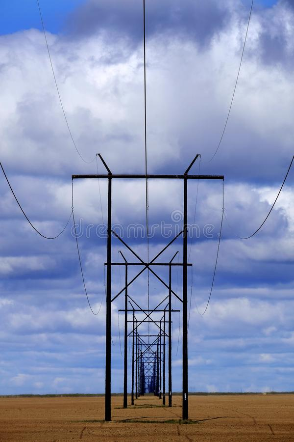Powerlines op Gebied met Blauwe Hemel en Wolken stock afbeelding