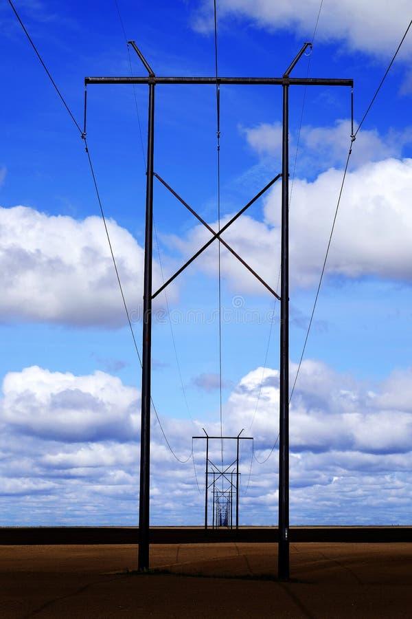 Powerlines op Gebied met Blauwe Hemel en Wolken royalty-vrije stock fotografie