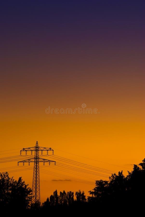 Powerpole in der orange purpurroten Sonnenuntergangleuchte lizenzfreie stockbilder