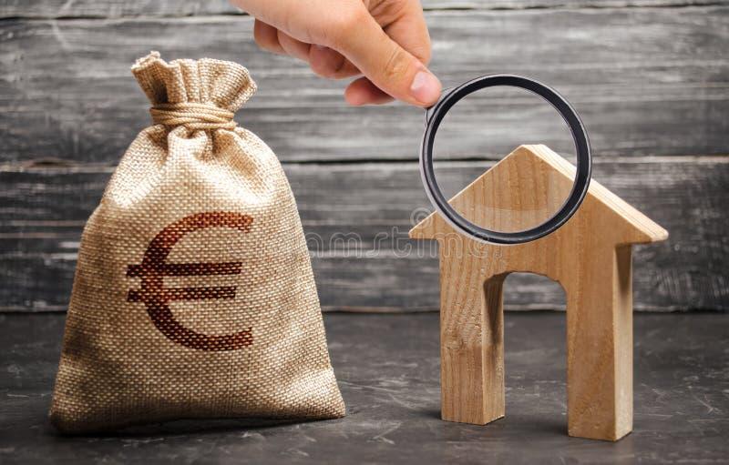 Powiększać - szkło jest przyglądający dom z wielkim drzwi i torbą z euro pieniądze Podatki, do wynajęcia dochód Budować domy zdjęcia stock