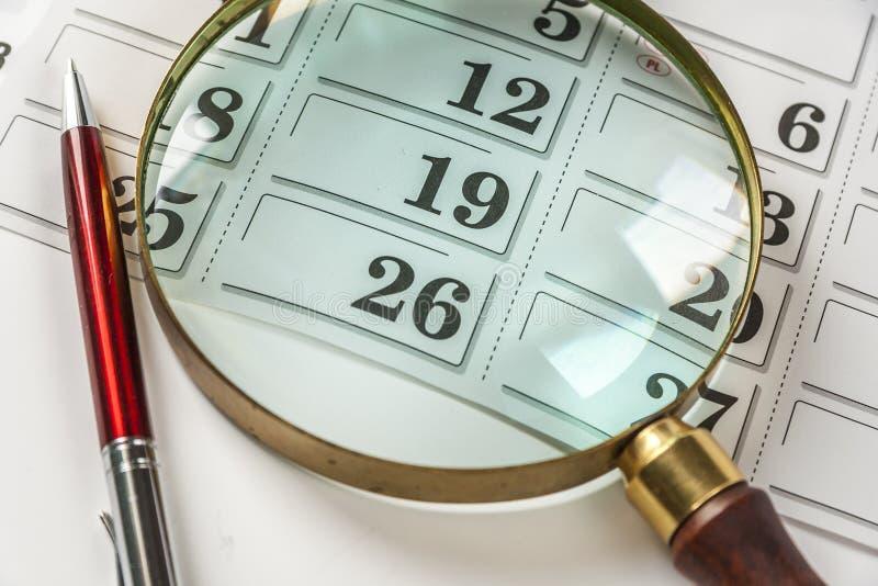 Powiększać - szkło I pióro Na kalendarzu obraz stock