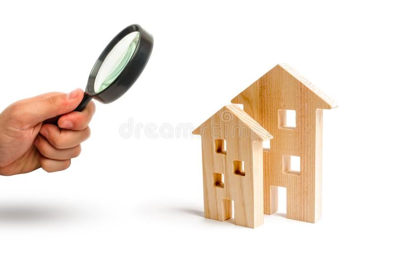Powiększać - szkło jest przyglądający Drewniani domy na białym tle Rosnący popyt dla mieścić i nieruchomości Przyrost obraz royalty free