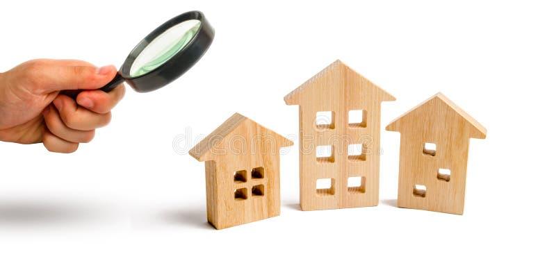 Powiększać - szkło jest przyglądający Drewniani domy na białym tle Rosnący popyt dla mieścić i nieruchomości Przyrost fotografia stock