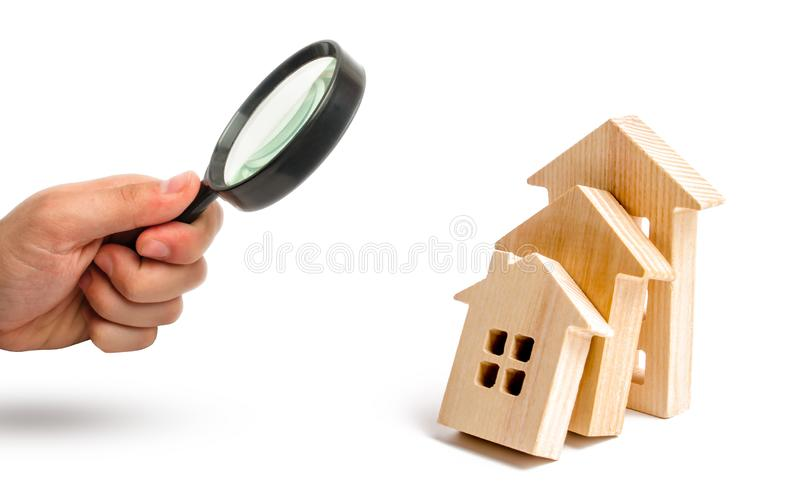 Powiększać - szkło jest przyglądający Drewniani domy spada na each inny jak domina pojęcie spada ceny dla domowego zakupu zdjęcia royalty free