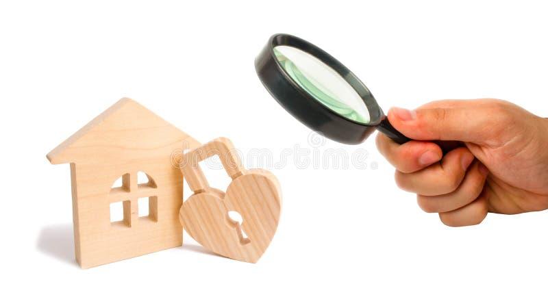 Powiększać - szkło jest przyglądający Drewniany dom z serce kształtującym kędziorkiem na białym tle Miłości gniazdeczko, związki  obraz royalty free