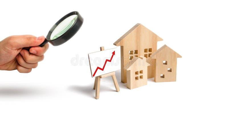 Powiększać - szkło jest przyglądający Drewniany domu stojak z czerwoną strzałą w górę Rosnący popyt dla mieścić i nieruchomości P obraz royalty free