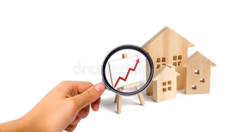 Powiększać - szkło jest przyglądający Drewniany domu stojak z czerwoną strzałą w górę Rosnący popyt dla mieścić i nieruchomości P zdjęcie stock